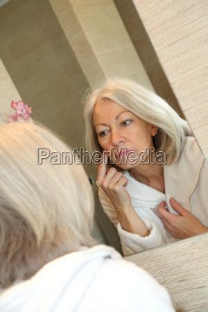 starszy kobiety stosujace krem u200bu200bnawilzajacy na
